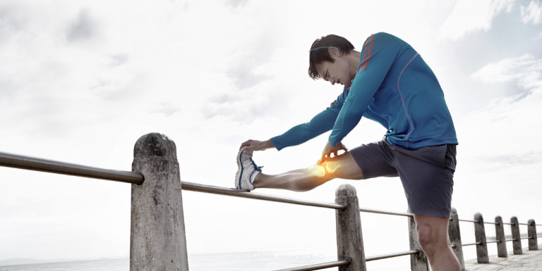 Image of jogger stretching on a beachfront boardwalk.